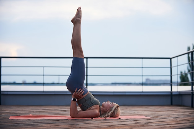 Młoda kobieta o blond włosach i szczupłym ciele zrobić ćwiczenia jogi na macie do jogi na drewnianym tarasie o zachodzie słońca.