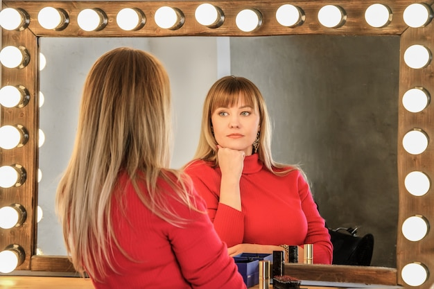 Młoda kobieta o blond włosach na czerwono na toaletce patrzy w zamyśleniu na swoje odbicie w lustrze.