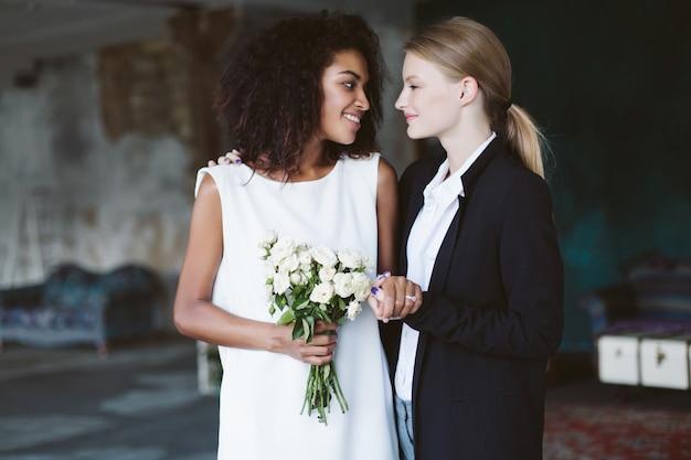 Młoda kobieta o blond włosach w czarnym garniturze i uśmiechnięta afroamerykanka z ciemnymi kręconymi włosami w białej sukni z bukietem kwiatów w dłoni szczęśliwie patrząc na siebie podczas ceremonii ślubnej