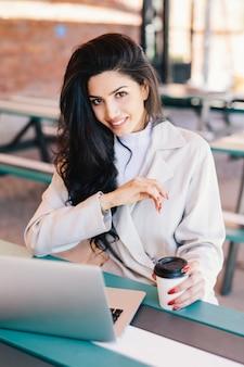 Młoda kobieta o ciemnych włosach, o jasnych oczach, pełnych ustach i zdrowej skórze, ubrana w biały płaszcz odpoczywający w kawiarni i przeglądający internet