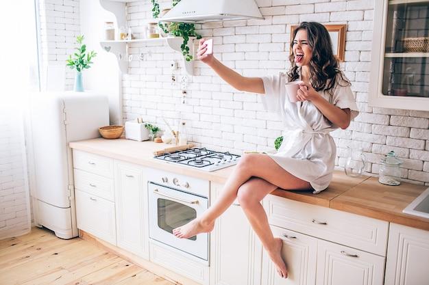 Młoda kobieta o ciemnych włosach siedzi na blacie w kuchni. robienie selfie i pokazywanie języka w aparacie. sam w kuchni. poranne światło dzienne. noś piękną suknię.