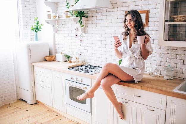 Młoda kobieta o ciemnych włosach siedzi w kuchni i przy użyciu telefonu sam. trzymaj kubek w rękach. brunetka nosić poranną suknię.