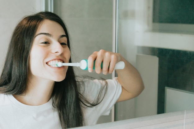 Młoda kobieta o czarnych włosach szczotkuje zęby elektryczną szczoteczką do zębów