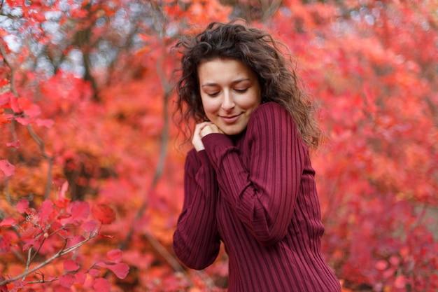 Młoda kobieta o czarnych włosach w czerwonym spocie ogrzewającym ręce, dmuchając w czerwone jesienne krzaki.