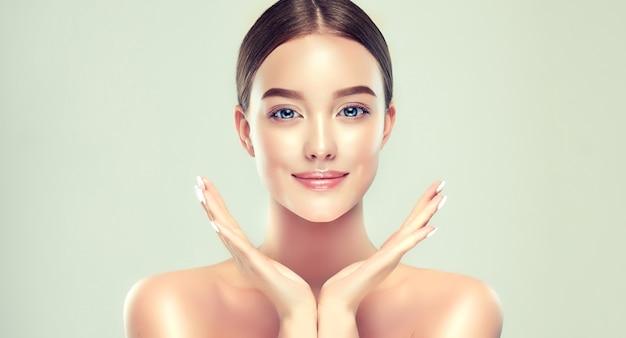 Młoda kobieta o czystej, świeżej skórze trzyma ręce w symetrycznej pozycji zabieg na twarz