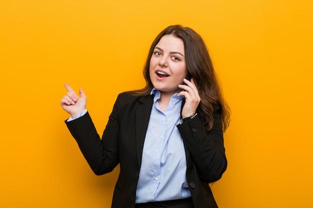 Młoda kobieta o dużych kształtach plus size z telefonem, uśmiechając się wesoło, wskazując palcem wskazującym daleko.