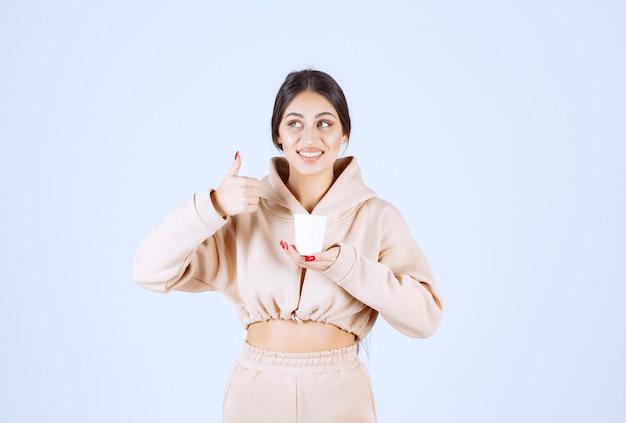 Młoda kobieta o filiżance kawy i pokazując znak przyjemności