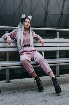 Młoda kobieta o futurystycznym wyglądzie siedzi na ławce dziewczyna z czarno-białymi warkoczykami na tle futurystycznego budynku