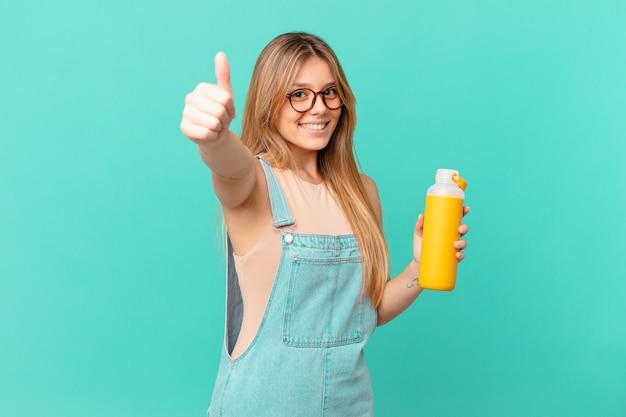 Młoda kobieta o gładkim poczuciu dumy, uśmiechająca się pozytywnie z kciukami w górę