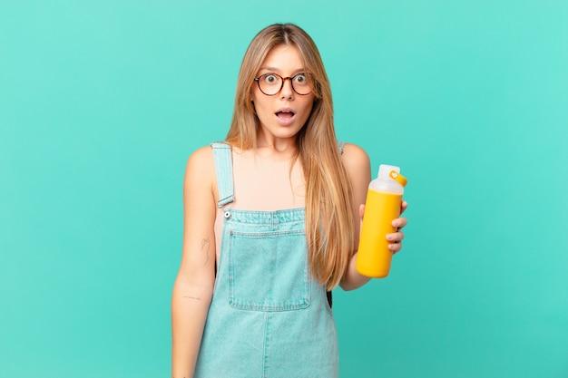 Młoda kobieta o gładkim wyglądzie wygląda na bardzo zszokowaną lub zdziwioną