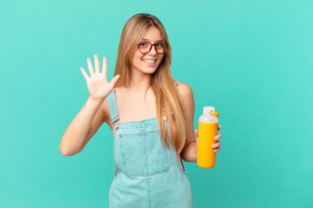 Młoda kobieta o gładko uśmiechniętym i przyjaznym wyglądzie, pokazująca numer pięć
