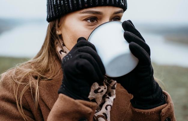 Młoda kobieta o gorący napój na świeżym powietrzu