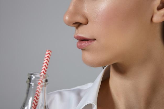 Młoda kobieta o idealnie czystej skórze z zakreślaczem, popijając sodę z whisky