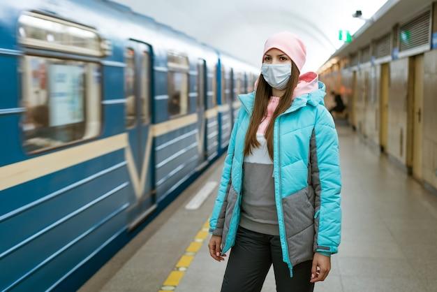 Młoda kobieta o kaukaskim wyglądzie w ciepłych ubraniach w metrze w masce ochronnej przed w...