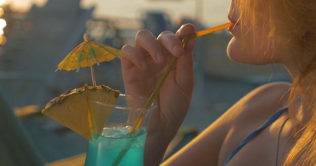 Młoda kobieta o koktajl na plaży o zachodzie słońca