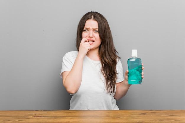 Młoda kobieta o krętych ustach, obgryzająca paznokcie, obolała i bardzo niespokojna