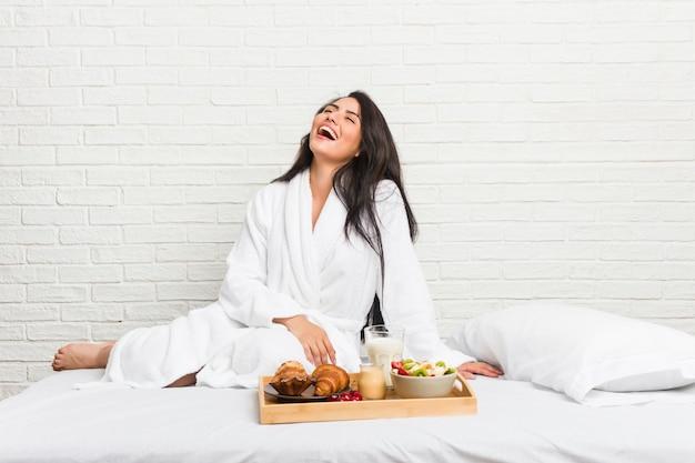 Młoda kobieta o krzywych kształtach, jedząca śniadanie na łóżku, zrelaksowana i szczęśliwa, śmiejąca się, szyja rozciągnięta, pokazująca zęby.