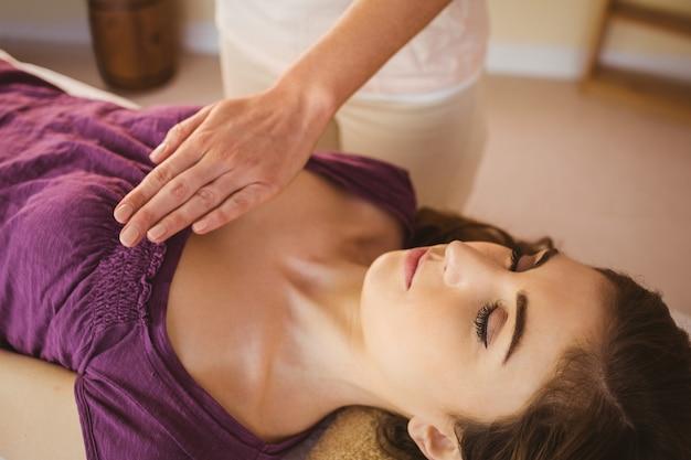 Młoda kobieta o leczeniu reiki w pokoju terapii