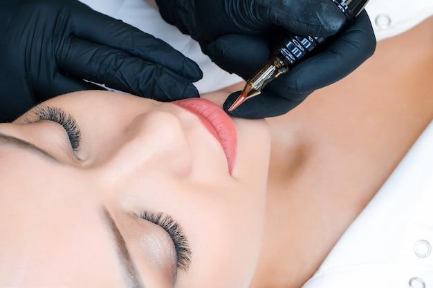 Młoda kobieta o makijaż permanentny na ustach w salonie kosmetycznym. naturalne zielone tło