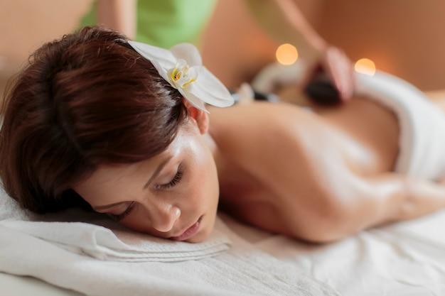 Młoda kobieta o masaż gorącymi kamieniami