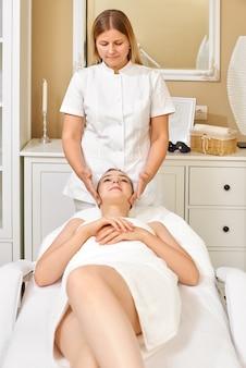 Młoda kobieta o masaż twarzy w gabinecie kosmetycznym
