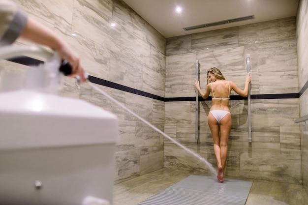 Młoda kobieta o masaż wysokociśnieniowy z prysznicem sharko. uzdatnianie wody, hydromasaż w nowoczesnym spa
