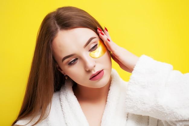 Młoda kobieta o pięknej skórze nakłada plastry do pielęgnacji skóry pod oczami
