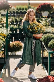 Młoda kobieta o pięknych blond włosach i delikatnym uśmiechu, ubrana w zieloną szatę z paskiem, pracuje w szklarni