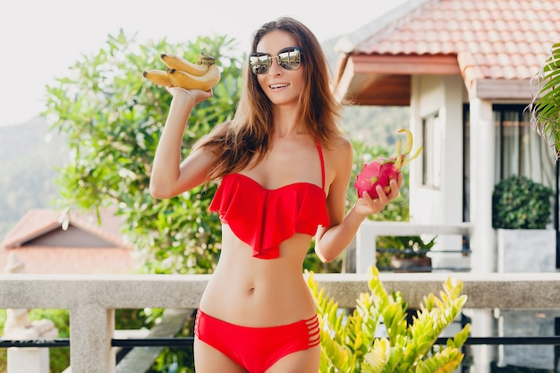 Młoda kobieta o pięknym, szczupłym ciele pozująca z tropikalnymi owocami, ubrana w czerwony strój kąpielowy bikini w tropikalnym kurorcie willi na wakacjach w azji, chuda sylwetka, trend w stylu letnim, dieta zdrowego stylu życia