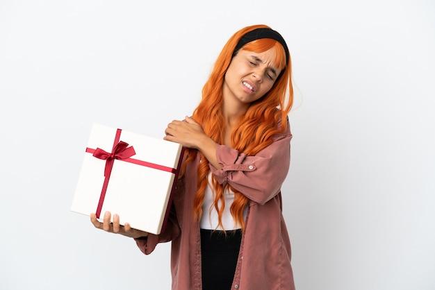 Młoda kobieta o pomarańczowych włosach trzymająca prezent na białym tle, cierpiąca na ból w ramieniu za wysiłek
