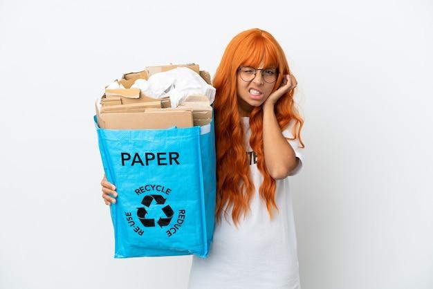 Młoda kobieta o pomarańczowych włosach trzymająca torbę do recyklingu pełną papieru do recyklingu na białym tle sfrustrowana i zakrywająca uszy