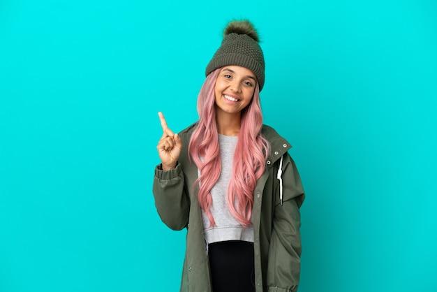 Młoda kobieta o różowych włosach, ubrana w przeciwdeszczowy płaszcz na białym tle na niebieskim tle pokazująca i unosząca palec na znak najlepszych