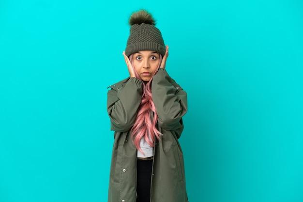 Młoda kobieta o różowych włosach, ubrana w przeciwdeszczowy płaszcz na niebieskim tle, sfrustrowana i zakrywająca uszy