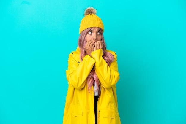 Młoda kobieta o różowych włosach, ubrana w przeciwdeszczowy płaszcz na niebieskim tle, zdenerwowana i przestraszona przykładająca ręce do ust