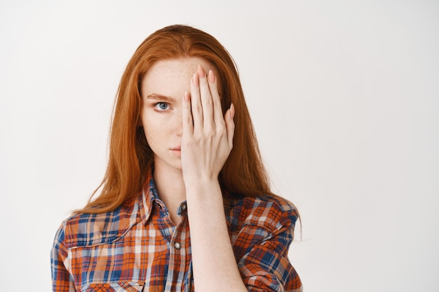 Młoda kobieta o rudych długich włosach i bladej skórze, zakrywająca połowę twarzy i wyglądająca poważnie z przodu, stojąca nad białą ścianą