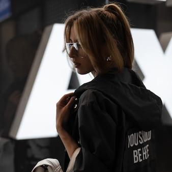 Młoda kobieta o rudych włosach z modną fryzurą w stylowych okularach w modnej kurtce ze skórzanym białym plecakiem w stylu vintage stoi przy szklanej ścianie w sklepie. atrakcyjna amerykańska dziewczyna