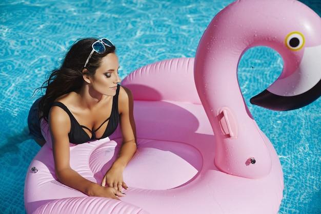 Młoda kobieta o seksownym ciele w czarnym bikini i okularach przeciwsłonecznych z nadmuchiwanym różowym flamingiem w basenie na świeżym powietrzu.