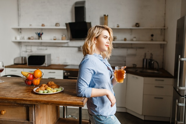 Młoda kobieta o śniadanie z rogalikami i ciasteczkami.