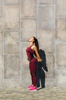 Młoda kobieta o sportowej sylwetce jest zaangażowana w ćwiczenia w pobliżu ściany na świeżym powietrzu w słoneczny letni poranek