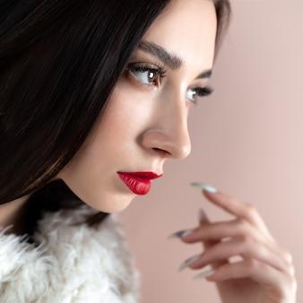 Młoda kobieta o wspaniałych kształtach brwi, długich rzęs i czerwonych ust. brunetka pozuje na białej ścianie.