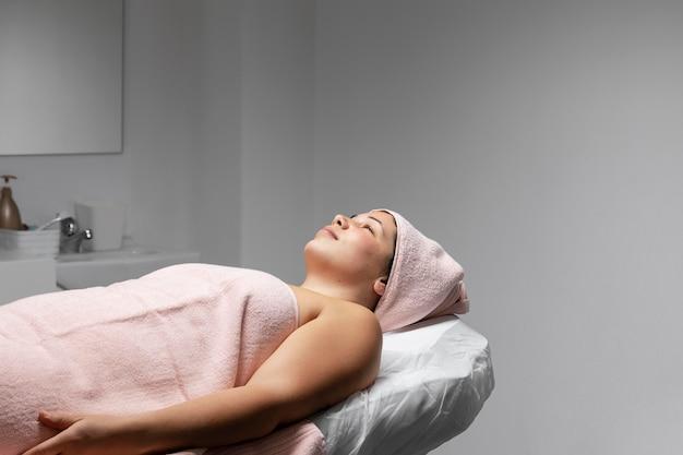 Młoda kobieta o zabieg na twarz w salonie kosmetycznym