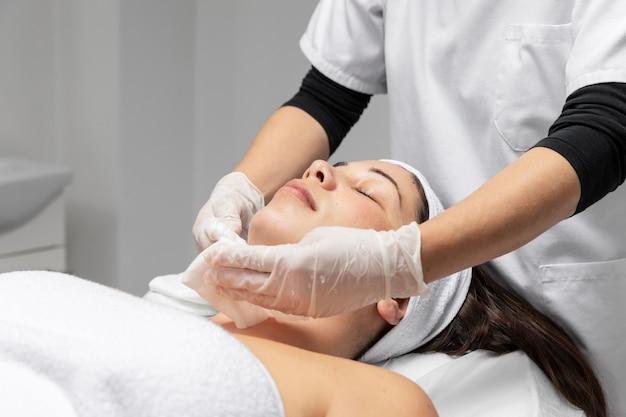 Młoda kobieta o zabiegu pielęgnacji skóry twarzy