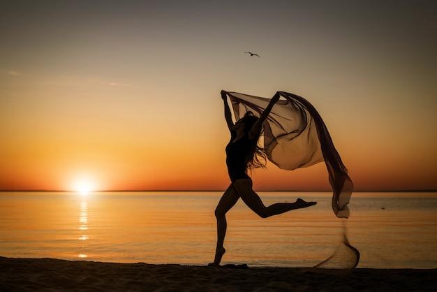 Młoda kobieta o zachodzie słońca, skoki nad brzegiem morza z ściereczką na tle nieba