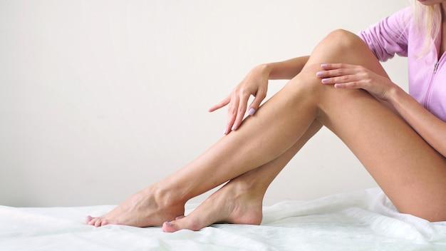 Młoda kobieta o zadbanym ciele po woskowaniu ma gładkie jedwabiste nogi