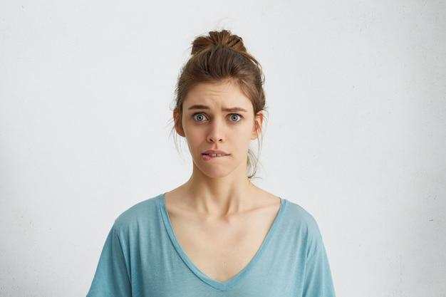 Młoda kobieta o zmartwionym spojrzeniu, przygryzająca dolną wargę, nerwowo spoglądająca niebieskimi, niespokojnymi oczami