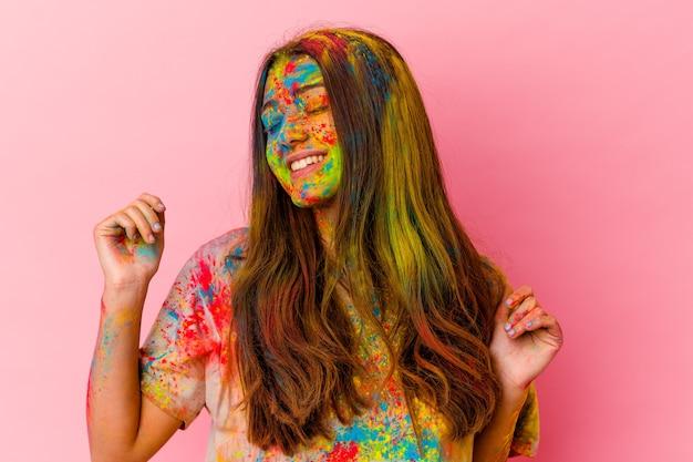 Młoda kobieta obchodzi święto na białym tle na białej ścianie, taniec i zabawę