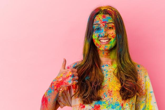 Młoda kobieta obchodzi święto na białym tle na białej ścianie, uśmiechając się i podnosząc kciuk do góry