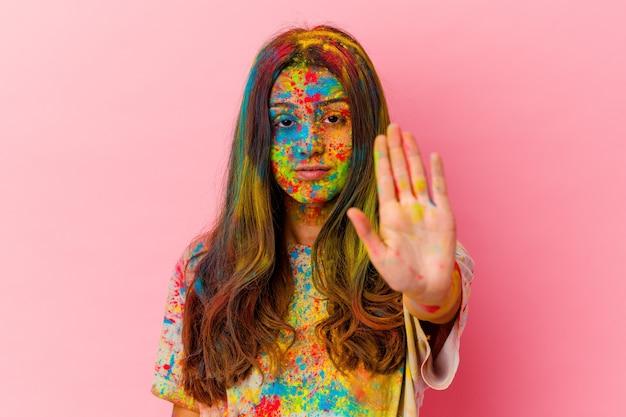 Młoda kobieta obchodzi święto święta na białym tle na białej ścianie stojącej z wyciągniętą ręką pokazując znak stopu, uniemożliwiając ci