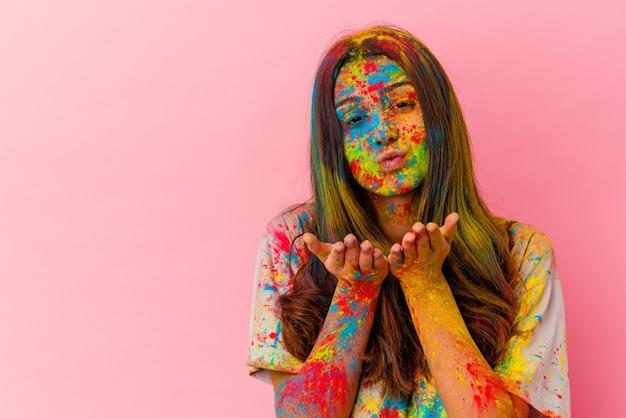 Młoda kobieta obchodzi święty festiwal na białym tle na białej ścianie składane usta i trzymając dłonie, aby wysłać pocałunek powietrza