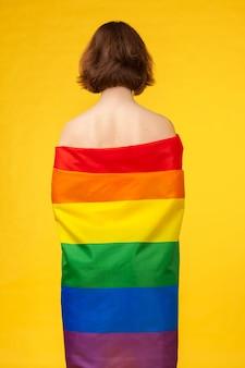 Młoda kobieta obejmujące flagą dumy lgbt